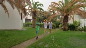 Padres y niño que corren en la yarda debajo de la lluvia metrajes
