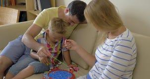 Padres y niño que juegan al juego de la pesca en casa almacen de video