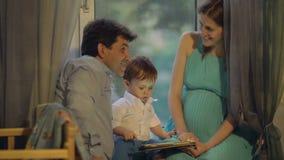 Padres y niño que juegan en la almohadilla táctil en casa almacen de video