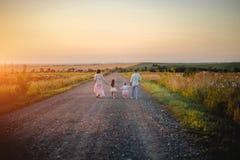 Padres y niños al aire libre en la puesta del sol fotografía de archivo