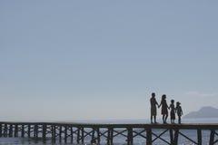Padres y niños de la silueta que llevan a cabo las manos en el embarcadero Fotos de archivo libres de regalías