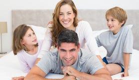 Padres y niños felices en cama fotos de archivo libres de regalías