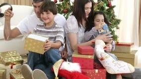 Padres y niños que abren regalos de Navidad almacen de video