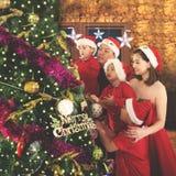 Padres y niños que adornan un árbol de navidad Imagenes de archivo