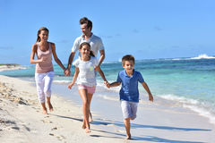 Padres y niños que corren en el goce de la playa Imagen de archivo