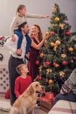 Padres y niños que embellecen el árbol de navidad Imagen de archivo