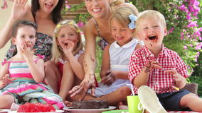 Padres y niños que gozan de la torta de chocolate en el partido almacen de metraje de vídeo