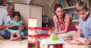 Padres y niños que juegan con los juguetes en dormitorio almacen de metraje de vídeo