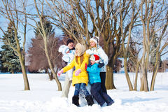 Padres y niños que juegan en nieve Foto de archivo