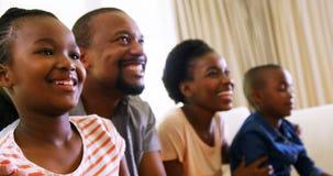 Padres y niños que juegan a los videojuegos en sala de estar metrajes