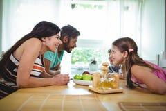 Padres y niños que parecen cara a cara y sonrisa Fotos de archivo