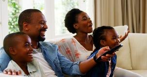 Padres y niños que se divierten mientras que mira la televisión en sala de estar almacen de video