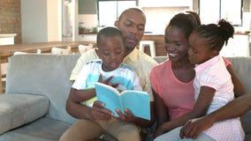 Padres y niños que se sientan en la lectura del sofá metrajes