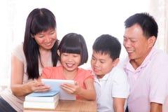 Padres y niños que usan la PC de la tablilla junto. Imagen de archivo
