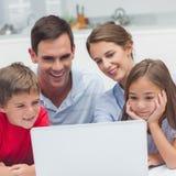 Padres y niños que usan un ordenador portátil Imagen de archivo