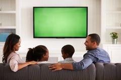 Padres y niños que ven la TV, mirando uno a foto de archivo libre de regalías