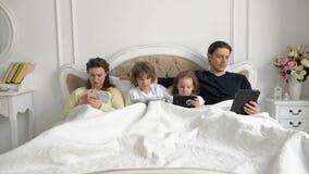 Padres y niños usando los dispositivos móviles junto en el dormitorio durante fin de semana en casa Los jóvenes se juntan con los metrajes