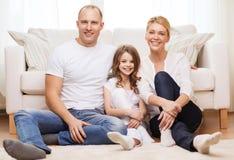 Padres y niña que se sientan en piso en casa Fotografía de archivo libre de regalías