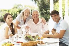 Padres y niños adultos que gozan de Al Fresco Meal Foto de archivo libre de regalías
