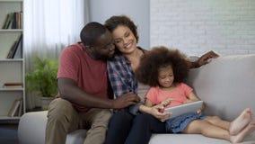Padres y pocas historietas de observación de la hija en la tableta, familia feliz junto imágenes de archivo libres de regalías