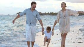 Padres y su niño que caminan a lo largo de la playa almacen de video