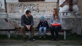 Padres y su niño que se sientan en el banco cerca almacen de metraje de vídeo