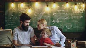 Padres y sus lenguas de la demostración del hijo en la sala de clase Aprendizaje de concepto Alumnos en uniforme Profesor en sala almacen de metraje de vídeo