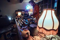 Padrone caucasico in kimono che produce tè naturale nella stanza scura con un interno di legno Tradizione, salute, armonia immagini stock