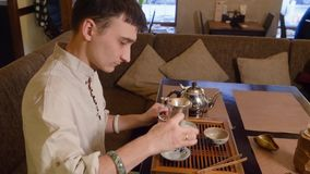 Padrone del tè facendo uso di acqua calda per la ciotola del tè ed il lanciatore di riscaldamento di imparzialità a cerimonia video d archivio