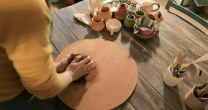 Padrone del vasaio della femmina adulta che prepara l'argilla sulla tavola, primo piano, vista superiore archivi video