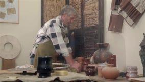 Padrone dell'argilla che preparring la sua area di lavoro stock footage