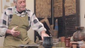 Padrone dell'argilla che preparring la sua area di lavoro video d archivio