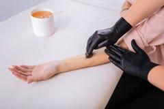 Padrone depilatorio professionale che mette cera sul braccio del suo cliente fotografie stock
