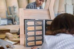 Padrone di produzione della mobilia che fa sedia di legno, progettista femminile con i campioni di legno che scelgono rifinitura  fotografie stock