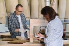 Padrone di produzione della mobilia che fa sedia di legno, progettista femminile con i campioni di legno che scelgono rifinitura  fotografia stock