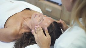 Padrone qualificato di massaggio che fa lifting facciale nel salone della stazione termale archivi video