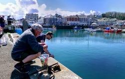 Padstow Cornwall, April 11th 2018: Två män som fiskar eller fångar krabbor Arkivfoton