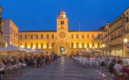 Padua - fyrkant och Torre del Orologio (astronomiskt klockatorn) för piazzadeiSignori i bakgrunden i aftonskymning Arkivfoton