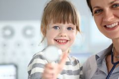 Paediatric doctor holding and hugging little cute girl patient stock images