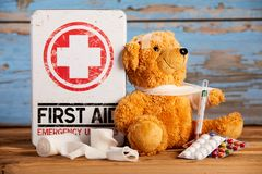 Paediatric First Aid and healthcare concept. With a little teddy with its arm in a sling alonge a medical kit with bandages, pills and hypodermic on rustic wood Royalty Free Stock Image