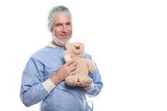 Paediatrician de sorriso amigável que guarda um urso de peluche foto de stock