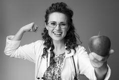 Paediatrist woman giving an apple and showing biceps on. Happy paediatrist woman in white medical robe giving an apple and showing biceps isolated on royalty free stock photography