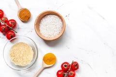 Paella μαγειρέματος με τα λαχανικά και τα συστατικά ρυζιού στο άσπρο γραφείων πρότυπο άποψης υποβάθρου τοπ Στοκ Εικόνες