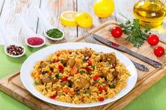 Paella avec de la viande, le poivre, les légumes et les épices sur le plateau Image libre de droits