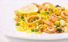Paella avec le poulet et fruits de mer d'un plat blanc Photo libre de droits
