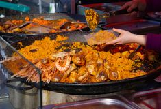 Paella being served from a large pan at a farmers market royalty free stock photo