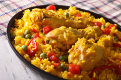 Paella with chicken drumsticks and vegetables close-up. horizont Stock Images