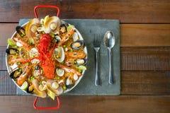 Paella com lagosta, os moluscos, os mexilhões e cal frescos Foto de Stock Royalty Free