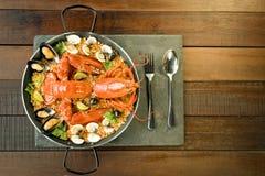 Paella com lagosta, os moluscos, os mexilhões e cal frescos Fotografia de Stock Royalty Free