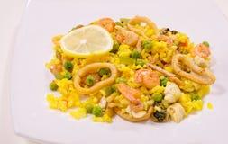 Paella con il pollo ed i frutti di mare, fondo bianco Immagine Stock